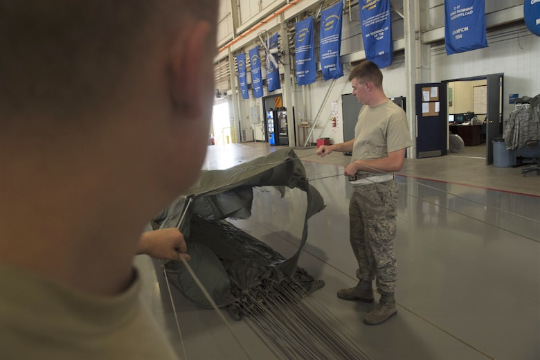 U.S. Air Force Senior Airmen Joshua Harris, an aerial operations apprentice assigned to the 97th LRS, and U.S. Air Force Senior Airman William Plate, an aerial operations apprentice assigned to the 97th LRS inspect a parachute after a recent air drop, July 11, 2018, at Altus Air Force Base, Okla.