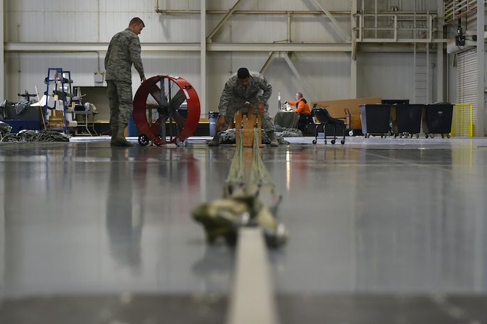 U.S. Air Force Senior Airman Allen Cook, an air freight specialist assigned to the 97th Logistics Readiness Squadron, separates cargo parachute strings to inspect it for damages, Feb. 12, 2018, at Altus Air Force Base, Okla.