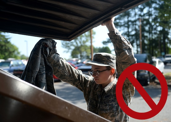 A woman in the Airman Battle Uniform is putting a blouse in to a dumpster.
