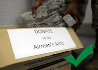 "Hands are putting an Airman Battle Uniform blouse into a donation box reading ""DONATE to the Airman's Attic."""