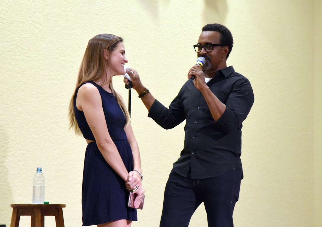 Lauren Headrick, spouse of U.S. Air Force Capt. Ryan Headrick, 85th Engineering Installation Squadron operations flight commander, assists Tim Meadows, actor and comedian, during his performance at the Bay Breeze Event Center at Keesler Air Force Base, Mississippi, July 14, 2018. Meadows is also an alumni of the late-night comedy show, Saturday Night Live. (U.S. Air Force photo by Kemberly Groue)