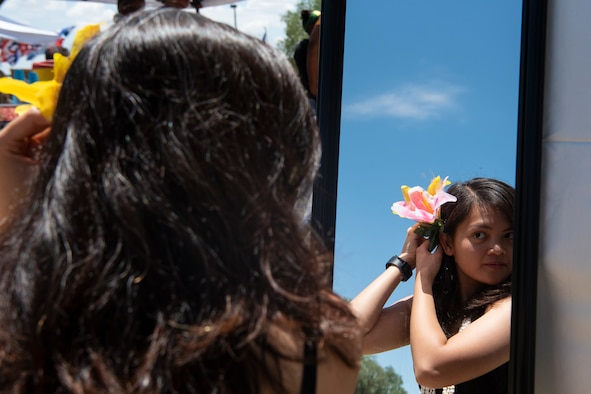 Airman 1st Class Crissea Ramirez, 27th Special Operations Communication Squadron cyber operations technician, puts a flower in her hair before her performance during Wing Culture Day at Cannon Air Force Base N. M., July 12, 2018. Airman Ramirez performed with the Air Commando Polynesian Dance Club for Wing Culture Day.