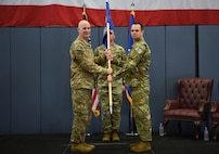 Colonel John Grimm, 90th Security Forces Group commander, passes the guidon to Maj. Jaroslaw Zrodlowski, 790th Missile Security Forces Squadron commander, during the 790th MSFS assumption of command ceremony at F.E. Warren Air Force Base, Wyo., July 17, 2018. The ceremony signified the assumption of command and formal transfer of authority to Zrodlowski. (U.S. Air Force photo by Airman 1st Class Abbigayle Wagner)