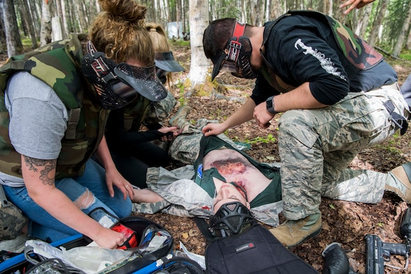 Personnel from the 673d Medical Group search for injuries during the practical application of the Tactical Combat Casualty Care course at the Warrior Extreme Paintball course at Joint Base Elmendorf-Richardson, Alaska, July 13, 2018. The course is an opportunity for every student to provide care under fire, perform tactical field care on those who are injured and execute a tactical evacuation.