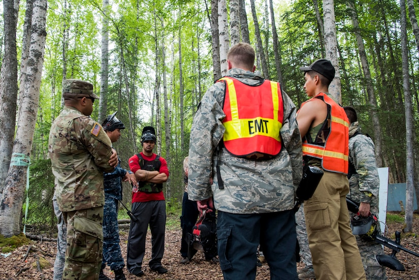 Tactical Combat Casualty Care instructors discuss strategic plans during the practical application of the TCCC course at the Warrior Extreme Paintball course at Joint Base Elmendorf-Richardson, Alaska, July 13, 2018. The course is an opportunity for every student to provide care under fire, perform tactical field care on those who are injured and execute a tactical evacuation.