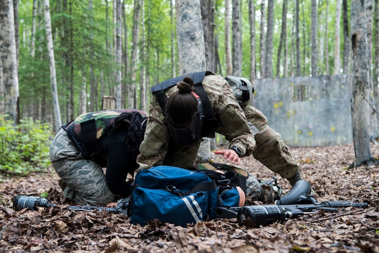 "Personnel from the 673d Medical Group take cover and protect the ""patient"" while under fire during the practical application of the Tactical Combat Casualty Care course at the Warrior Extreme Paintball course at Joint Base Elmendorf-Richardson, Alaska, July 13, 2018. The course is an opportunity for every student to provide care under fire, perform tactical field care on those who are injured and execute a tactical evacuation."