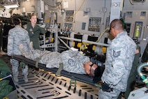 U.S. Air Force Reserve members with the 624th Aeromedical Staging Squadron receive instructions from U.S. Air Force Staff Sgt. Jodi Signer, an instructor from the 446th Aeromedical Evacuation Squadron, while loading a simulated patient onto a U.S. Air Force C-17 Globemaster III aircraft at U.S. Coast Guard Air Station Barbers Point, Hawaii, July 10, 2018, during Pacific Lifeline 2018.