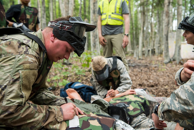 Personnel from the 673d Medical Group write an assessment during the practical application of the Tactical Combat Casualty Care course at the Warrior Extreme Paintball course at Joint Base Elmendorf-Richardson, Alaska, July 13, 2018. The course is an opportunity for every student to provide care under fire, perform tactical field care on those who are injured and execute a tactical evacuation.