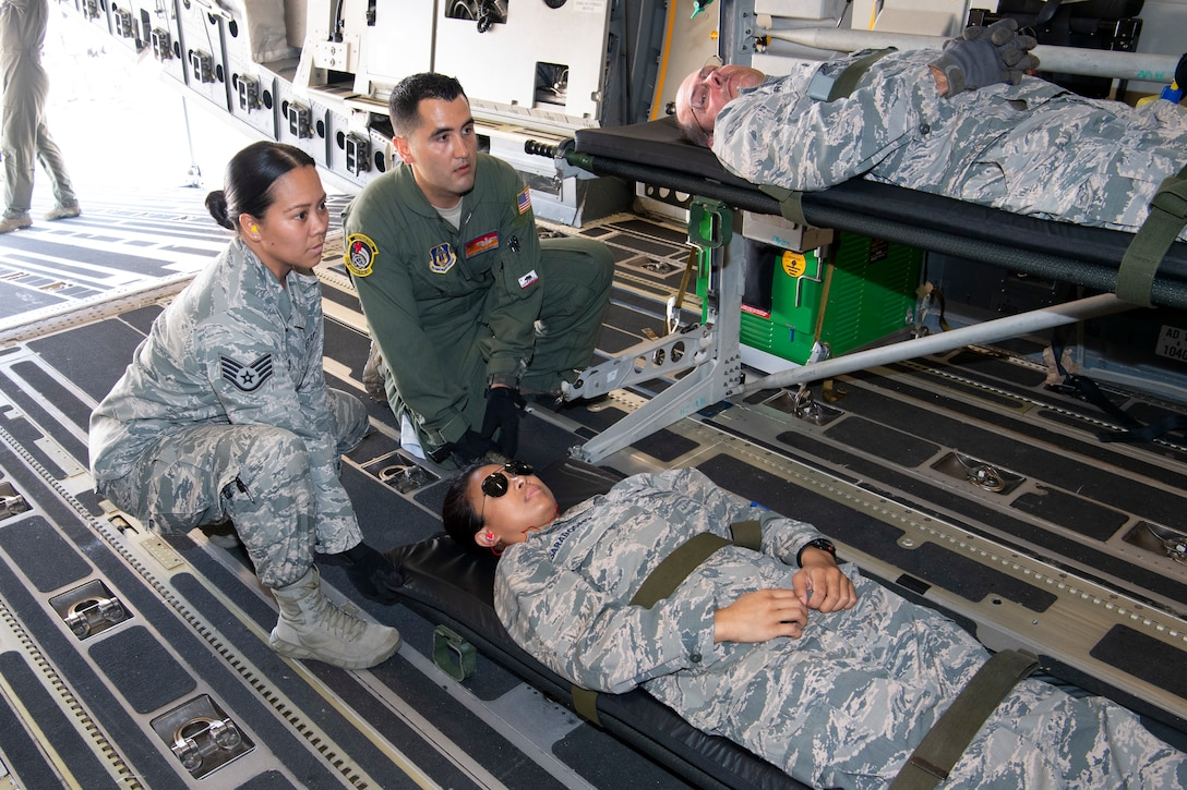 U.S. Air Force Master Sgt. Christian Amezcua, an instructor from the 452nd Aeromedical Evacuation Squadron, assists Staff Sgt. Shannon Guerrero, a medical technician with the 624th Aeromedical Staging Squadron, load a simulated patient onto a U.S. Air Force C-17 Globemaster III aircraft at U.S. Coast Guard Air Station Barbers Point, Hawaii, July 10, 2018, during Pacific Lifeline 2018.