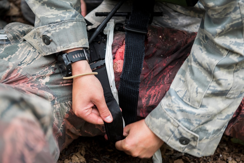 """Personnel from the 673d Medical Group apply a tourniquet to an injured """"patient"""" during the practical application of the Tactical Combat Casualty Care course at the Warrior Extreme Paintball course at Joint Base Elmendorf-Richardson, Alaska, July 13, 2018. The course is an opportunity for every student to provide care under fire, perform tactical field care on those who are injured and execute a tactical evacuation."""