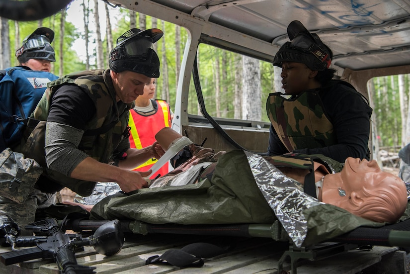 """Personnel from the 673d Medical Group cover the wounds of an injured """"patient"""" during the practical application of the Tactical Combat Casualty Care course at the Warrior Extreme Paintball course at Joint Base Elmendorf-Richardson, Alaska, July 13, 2018. The course is an opportunity for every student to provide care under fire, perform tactical field care on those who are injured and execute a tactical evacuation."""