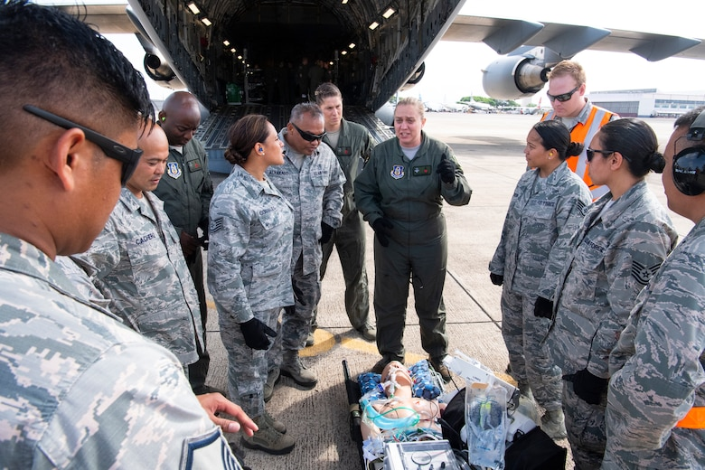 U.S. Air Force Maj. Venus Victorino, a member of the Critical Care Air Transport Team with the 943rd Aerospace Medicine Squadron, discusses critical-care patient transportation with 624th Aeromedical Staging Squadron personnel at U.S. Coast Guard Air Station Barbers Point, Hawaii, July 10, 2018, during Pacific Lifeline 2018. Pacific Lifeline 2018 is a statewide medical exercise in Hawaii conducted as part of a larger 2018 Rim of the Pacific Exercise.