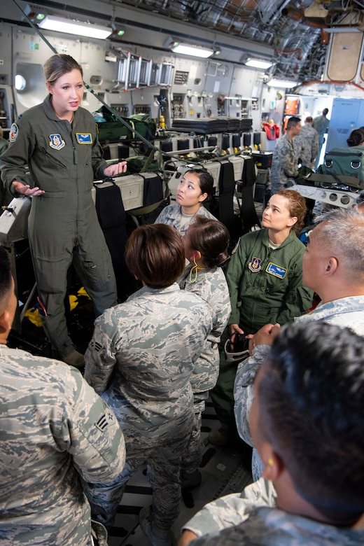 U.S. Air Force Capt. Jennifer Riportella, a flight nurse with the 446th Aeromedical Evacuation Squadron, discusses patient transport equipment used aboard a U.S. Air Force C-17 Globemaster III aircraft with 624th Aeromedical Staging Squadron personnel at U.S. Coast Guard Air Station Barbers Point, Hawaii, July 10, 2018, during Pacific Lifeline 2018.
