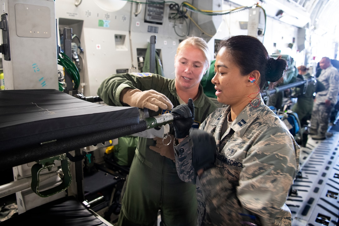U.S. Air Force Master Sgt. Michelle Geers, an aeromedical evacuation technician from the 315th Aeromedical Evacuation Squadron, demonstrates the locking mechanism for a litter used aboard a U.S. Air Force C-17 Globemaster III aircraft with Capt. Louisealbertine Sarabosing, a clinical nurse with the 624th Aeromedical Staging Squadron, at U.S. Coast Guard Air Station Barbers Point, Hawaii, July 10, 2018, during Pacific Lifeline 2018.