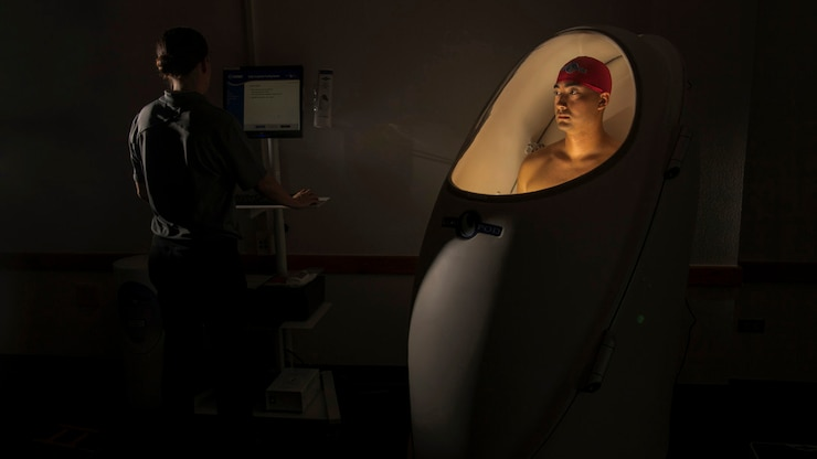 An airman stands in a lit pod-like contraption while another person looks on a screen next to him.