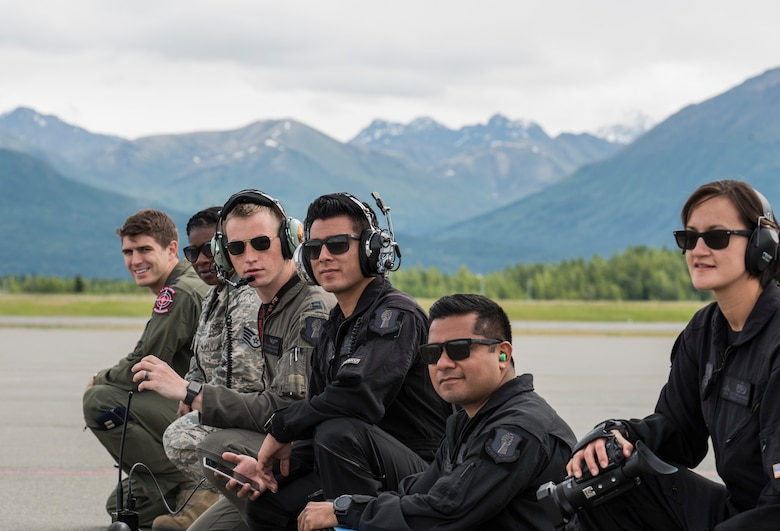 U.S. Air Force Airmen with the Pacific Air Forces' F-16 Demonstration Team and from Eielson Air Force Base, Alaska, watch an aerobatic practice prior to Arctic Thunder 2018, at Joint Base Elmendorf-Richardson, Alaska, June 26, 2018. The PACAF Demo Team worked hand-in-hand with Eielson AFB to perform at the air show while saving thousands of taxpayer dollars. (U.S. Air Force photo by Senior Airman Sadie Colbert)