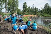 The Pacific Air Forces' F-16 Demonstration Team plants native vegetation by a riverbank with the Youth Employment in Parks program members in Anchorage, Alaska, June 29, 2018. The YEP program provides a 10-week summer program, hiring Anchorage teens to complete park improvement projects. Participants learn natural resource management job skills by building trails and restoring stream banks. (U.S. Air Force photo by Senior Airman Sadie Colbert)