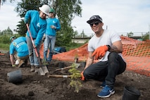 U.S. Air Force Staff Sgt. Mario Perez, a Pacific Air Forces' F-16 Demonstration Team avionics specialist, digs holes for tree saplings with the Youth Employment in Parks program members in Anchorage, Alaska, June 29, 2018. The demo team worked together to plant more than 30 saplings, which aids in strengthening riverbanks. (U.S. Air Force photo by Senior Airman Sadie Colbert)