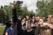 The Pacific Air Forces' F-16 Demonstration Team and Alaskan locals, take a selfie with Eddie P., the Anchorage Morning Show host, in Anchorage, Alaska, June 29, 2018. The team engaged with the community by participating in park beautification, conducting a meet-and-greet and attending a formlal dinner with the Anchorage, Alaska, city leaders. This afforded the team an opportunity to meet with their supporters and build trust and patriotism within the Alaskan community. (U.S. Air Force photo by Senior Airman Sadie Colbert)