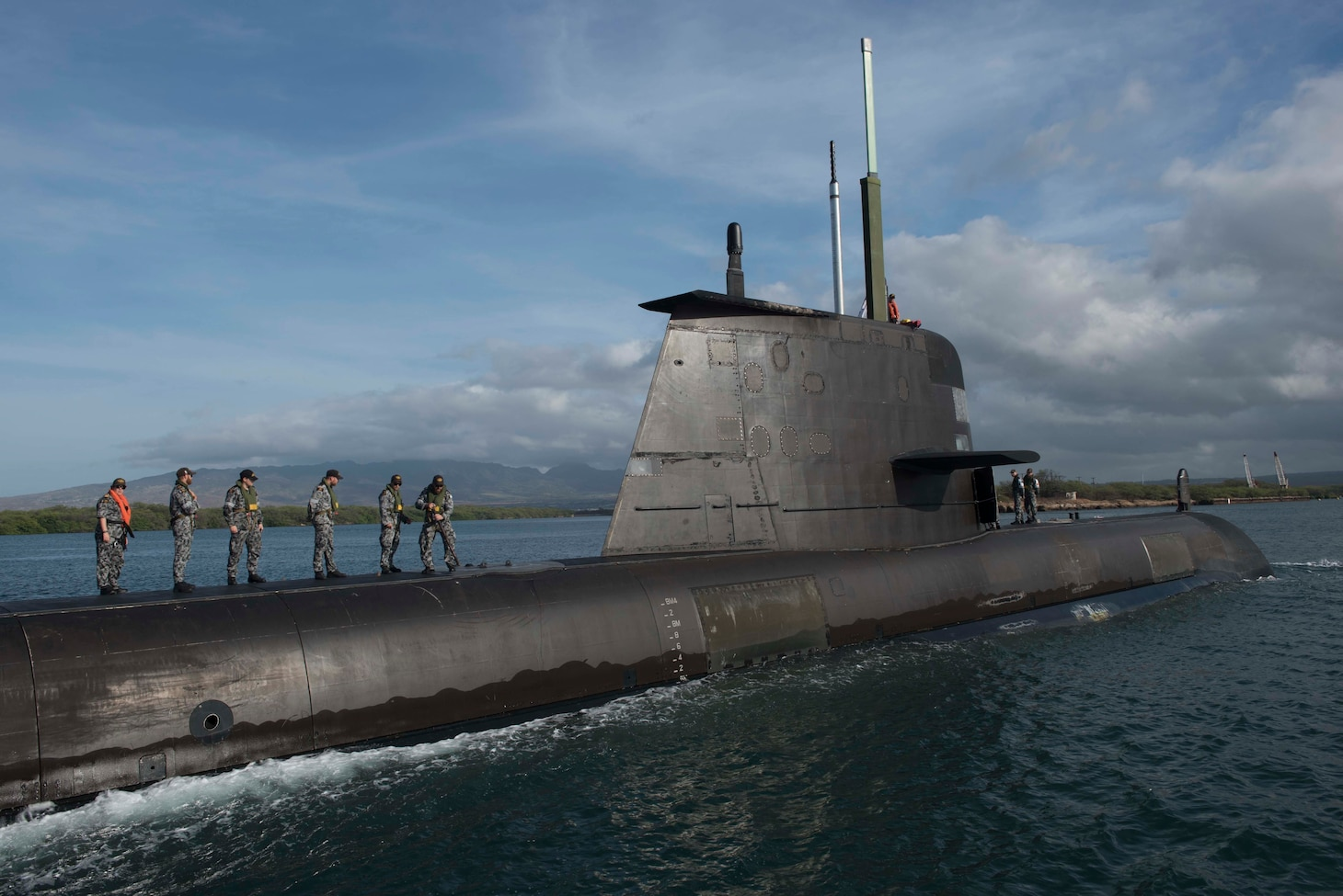 The crew of the Royal Australian Navy submarine HMAS Rankin stand on top of submarine while in the water.