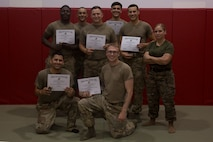 CAMP FOSTER, OKINAWA, Japan – Soldiers pose with their Marine instructor after earning their tan belts and certificates during Marine Corps Martial Arts Program training June 28 at Gunner's Gym aboard Camp Foster, Okinawa, Japan.