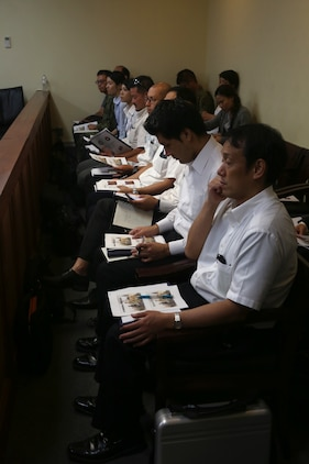 KADENA AIR BASE, OKINAWA, Japan – Representatives from local government agencies listen to trial procedures and read through information packets June 29 during a mock trial on Kadena Air Base, Okinawa, Japan.