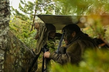 A Norwegian Coastal Ranger Commando conducts surveillance and reconnaissance from an observation point during Exercise Platinum Ren at Sorreisa, Norway, May 22, 2018. Marines with 1st Platoon, 1st Reconnaissance Battalion, 1st Marine Division, conducted the exercise in conjunction with KJKs to sustain mission essential tasks in a harsh operating environment and strengthen coalition partnerships.