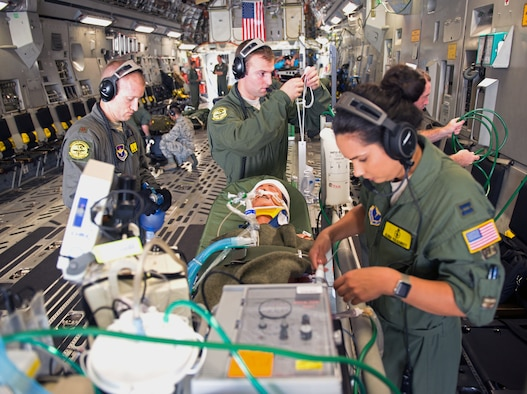 Maj. Mark Cheney (left),  59th Medical Wing anesthesiologist, Tech. Sgt. Bryan Sundstrom (middle), 59th MDW cardiopulmonary technician, and Capt. Elena Vulgamott (right), 59th MDW critical care registered nurse, prepare a simulated patient for transport during a Critical Care Air Transport Team demo at Joint Base San Antonio-Lackland, Texas, July 12, 2018. The transport teams are composed of medics who have gone through rigorous training to perform these high-stress and fast-paced missions. (U.S. Air Force photo by Senior Airman Stefan Alvarez)