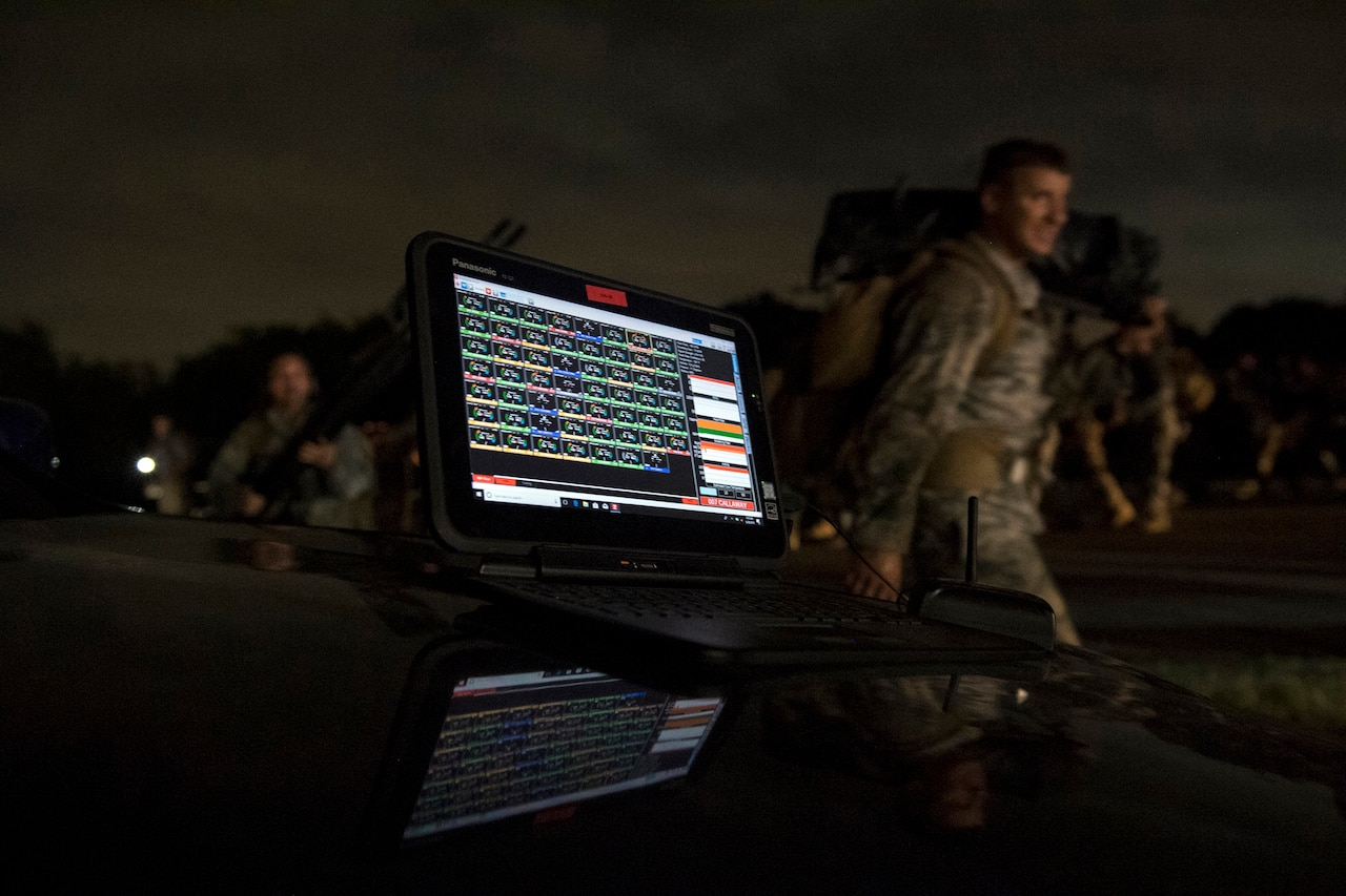 A computer screen displays data as airmen walk in the background.