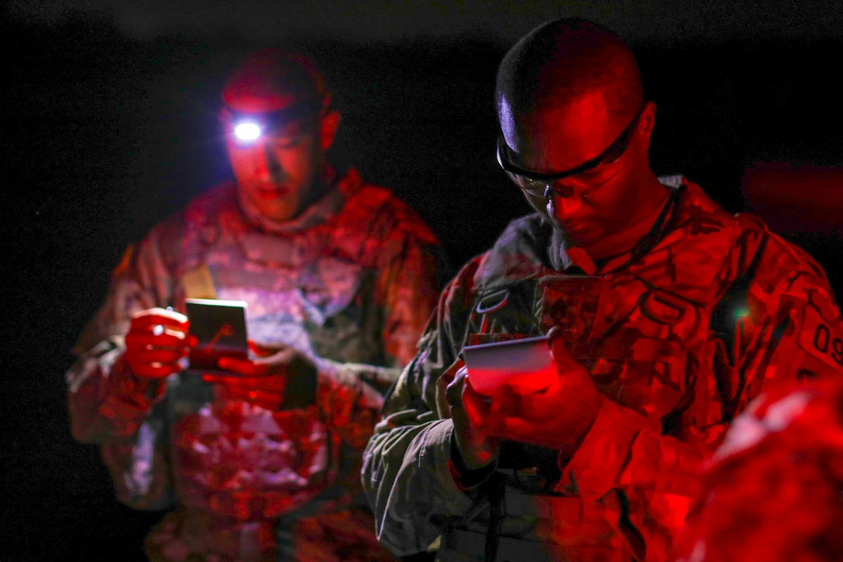 Two soldiers look at notepads at night.