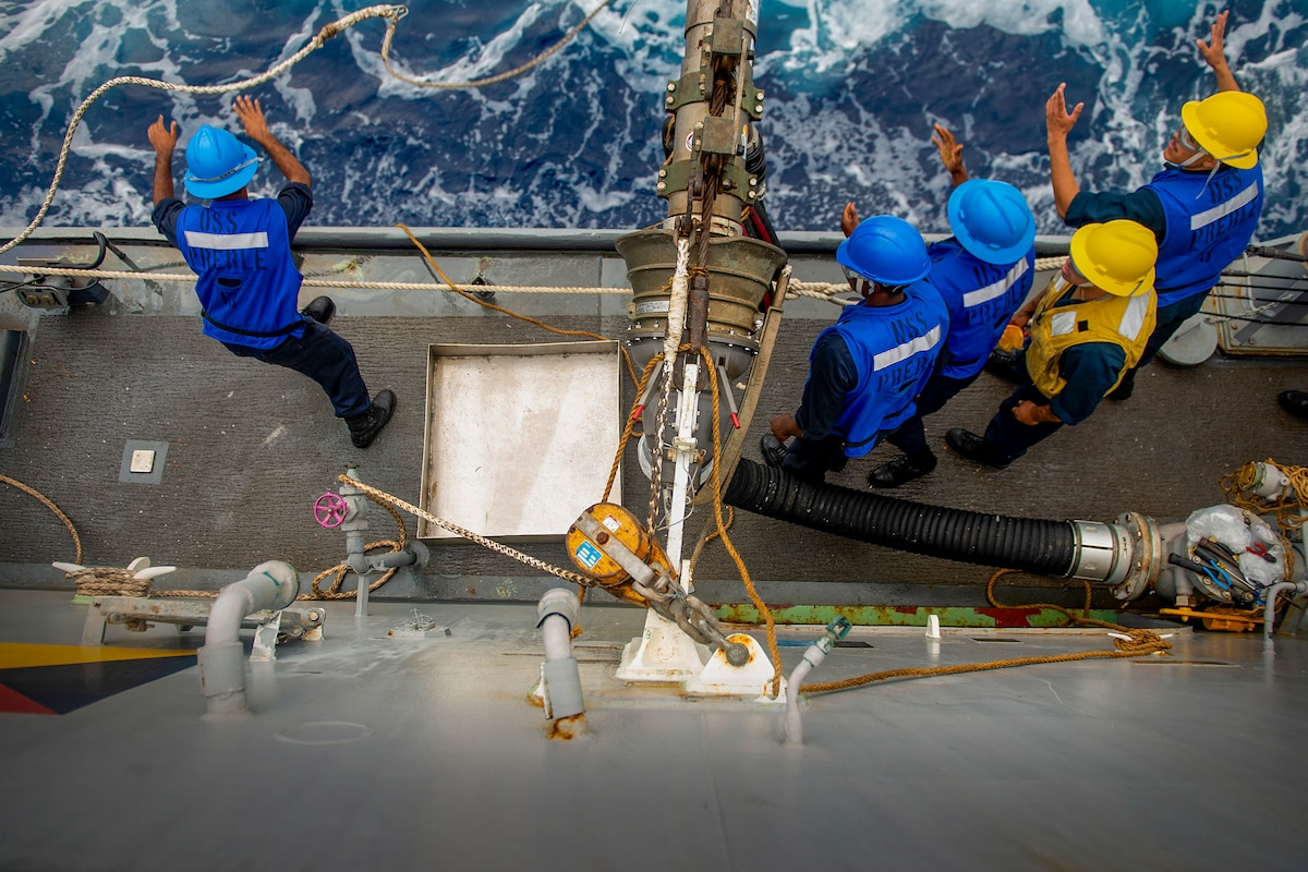 Sailors stand on the edge of a ship deck and throw a rope.
