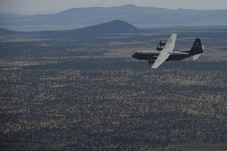 C-130J flying over countryside.
