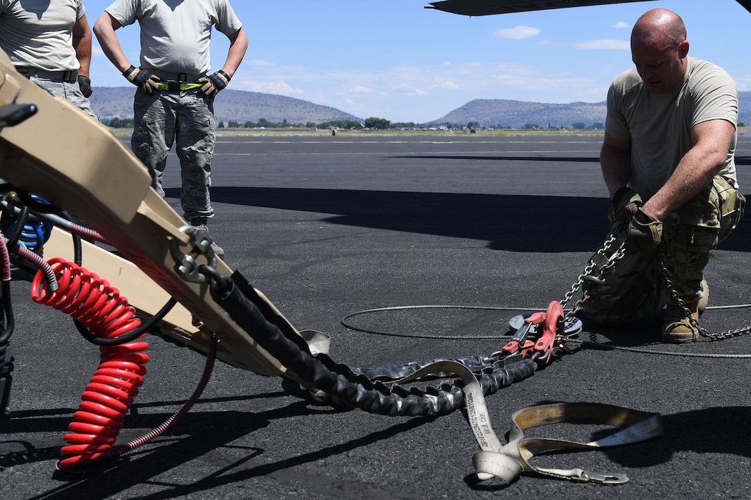 Airman connects cable from plane to chains of object.