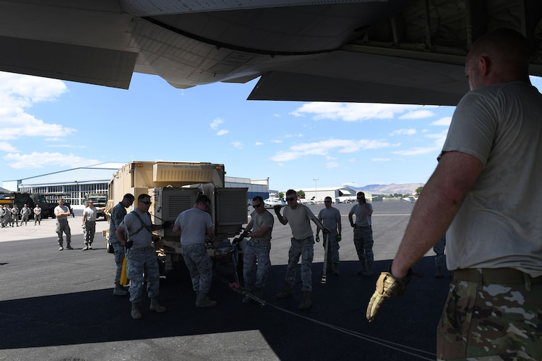 Airman directs other Airmen steering large object.