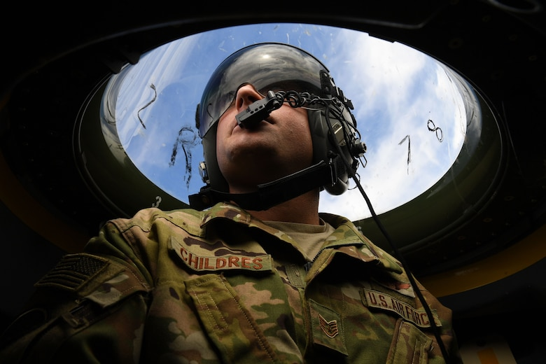 Airman looks over top of plane through plastic bubble.