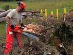 Airman uses a chainsaw to cut a fallen tree.