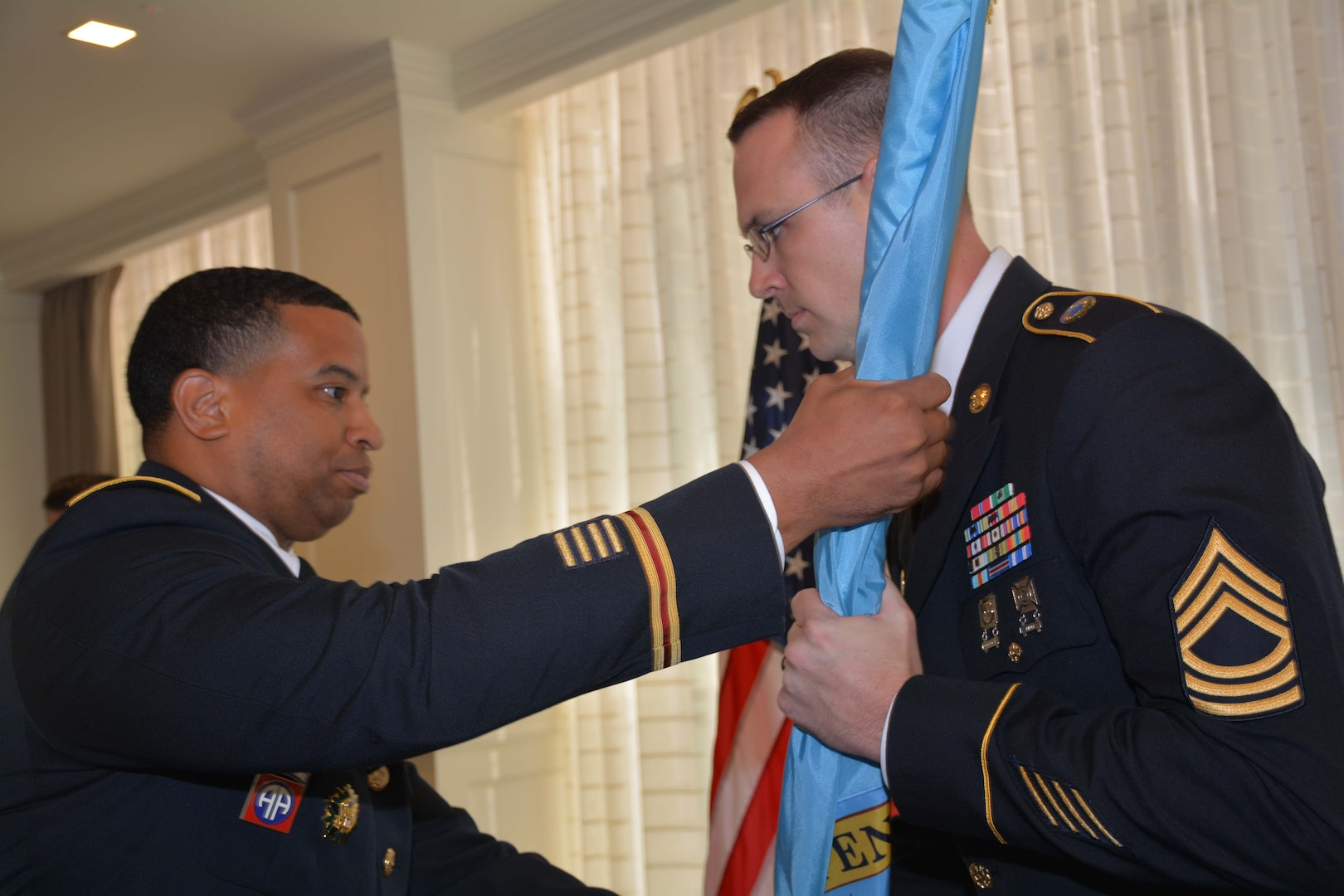 Army officer hands flag to Army NCO.