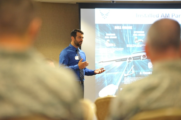Adam Ryba, representing the Air Force Rapid Sustainment Office, briefs an audience on the use of parts created through additive manufacturing (3-D printing) for Air Force aircraft.