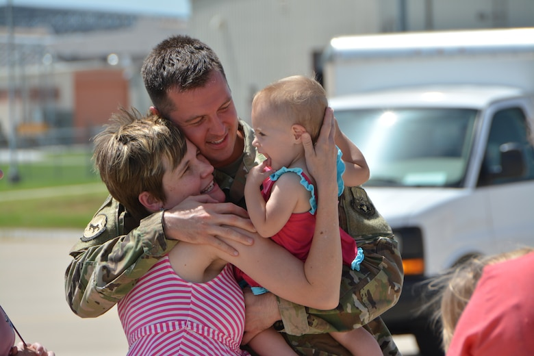 Staff Sgt. Noah Garris, a combat crew communications technician with the 507th Operations Support Squadron at Tinker Air Force Base, Okla., embraces his family following a deployment July 3, 2018. More than 100 Reserve Citizen Airmen from the 507th Air Refueling Wing at Tinker AFB deployed to Incirlik Air Base, Turkey, in support of air operations. (U.S. Air Force photo by Tech. Sgt. Samantha Mathison)