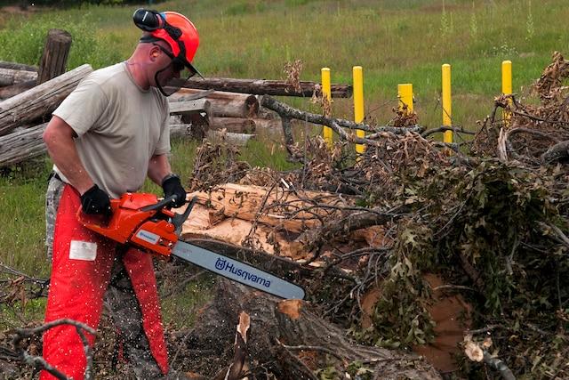 An Airman uses a chainsaw to cut debris.