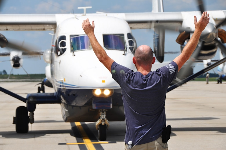 A maintainer signals a C-145 Skytruck aircrew as they taxi into their designated parking spot July 11, 2018 at Duke Field, Fla.