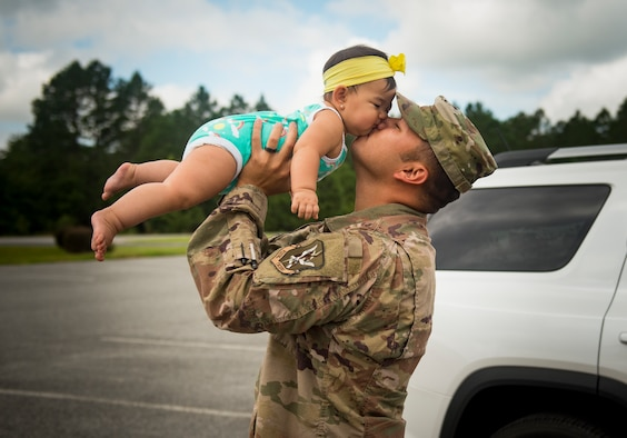 Tech. Sgt. Ramon Salas, 23d Aircraft Maintenance Squadron electrical and environmental craftsman, kisses his daughter Luna, July 9, 2018, at Moody Air Force Base, Ga. Airmen from the 75th Fighter Squadron (FS) and supporting units deployed to an undisclosed location in support of Operation Spartan Shield. (U.S. Air Force photo by Staff Sgt. Ceaira Tinsley)