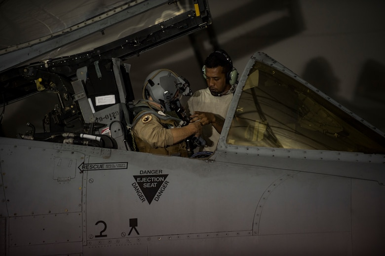 Senior Airman Daniel Ioane, 23d Aircraft Maintenance Squadron crew chief, assists an A-10C Thunderbolt II pilot with his harness, July 9, 2018, at Moody Air Force Base, Ga. Airmen from the 75th Fighter Squadron (FS) and supporting units deployed to an undisclosed location in support of Operation Spartan Shield. (U.S. Air Force photo by Andrea Jenkins)