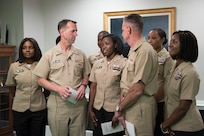 Chief of Naval Operations Adm. John M. Richardson (center left) and Chief of Naval Personnel Vice Adm. Robert P. Burke (center right) and Sailors assigned to the Pentagon announce new grooming standards on camera during a live all-hands call. The event was held to answer questions from the fleet and to announce upcoming changes and updates to Navy policies.