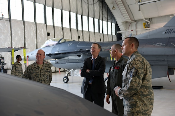 Gov. John Hickenlooper of Colorado, receives a brief on the Colorado Air National Guard's F-16 Falcon's mission capabilities from Col. Brian Turner, second from right, 140th Wing commander, at Buckley Air Force Base, Colorado, July 17, 2018.