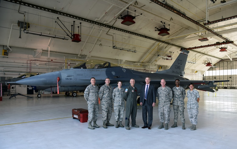 Members of Team Buckley stand with Gov. John Hickenlooper of Colorado in front of a F-16 Falcon assigned to the Colorado Air National Guard at Buckley Air Force Base, Colorado, July 17, 2018.