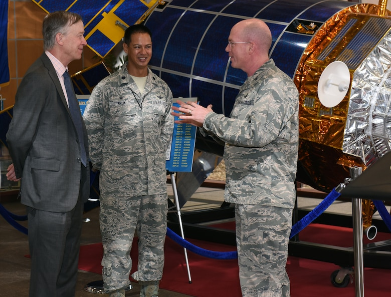 Gov. John Hickenlooper of Colorado, far left, receives a briefing from Col. Troy Endicott, far right, 460th Space Wing commander, and Lt. Col. Michael Kruk, 11th Space Warning Squadron commander, on the Space Based Infrared System in the Mission Control Station lobby at Buckley Air Force Base, Colorado, July 17, 2018.