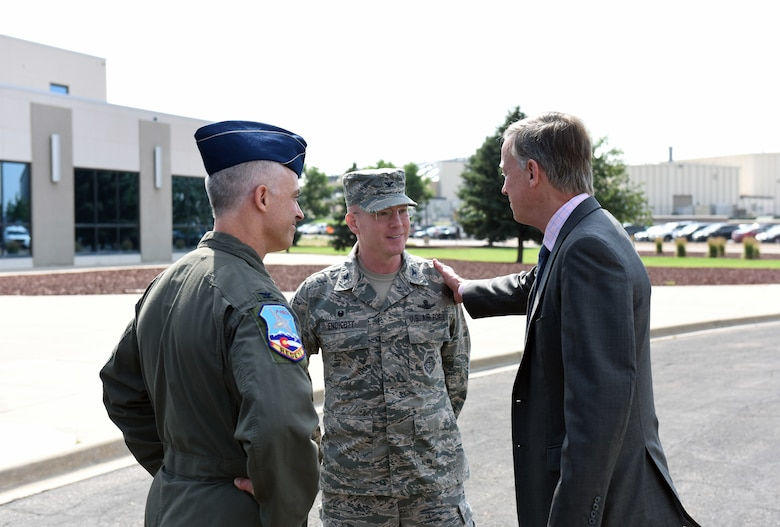 Gov. John Hickenlooper of Colorado, bids farewell to Col. Troy Endicott, center, 460th Space Wing commander, and Col. Brian Turner, far left, 140th Wing commander, following a visit at Buckley Air Force Base, Colorado, July 17, 2018.