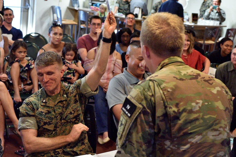U.S. Marine Corps Lt. Col. Earl Patterson, Marine Corps Detachment Goodfellow commander, holds up a card for U.S. Army Pvt. John Zeigler's, 344th Military Intelligence Battalion student, magic trick during the semi-annual Goodfellow's Got Talent show at the Crossroads Student Ministry Center on Goodfellow Air Force Base, Texas, July 13, 2018. Zeigler won first place for his performance. (U.S. Air Force photo by Senior Airman Randall Moose/Released)