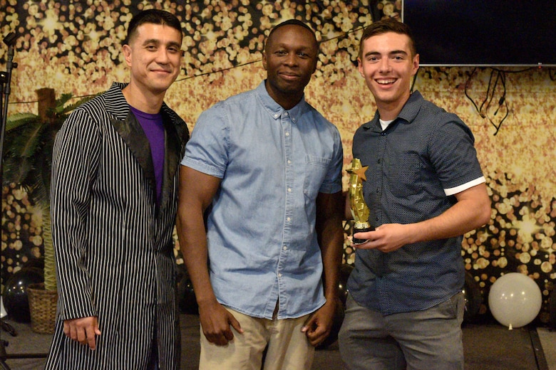 U.S. Air Force Col. Ricky Mills, 17th Training Wing commander and Chief Master Sgt. Lavor Kirkpatrick, 17th TRW command chief, present Airman 1st Class Dylan Hunter, 316th Training Squadron student, an award for the semi-annual Goodfellow's Got Talent show at the Crossroads Student Ministry Center on Goodfellow Air Force Base, Texas, July 13, 2018. Hunter won third place for his performance. (U.S. Air Force photo by Senior Airman Randall Moose/Released)